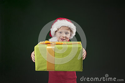 Boy with christmas hat and present on dark green