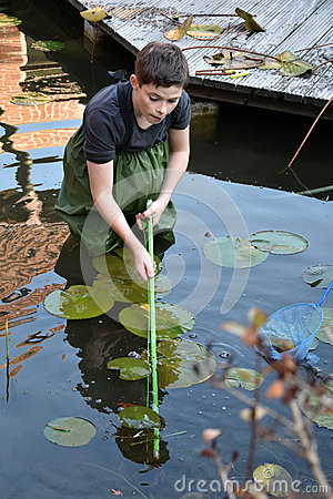 Free Boy Cleaning Garden Pond Royalty Free Stock Photography - 79714587