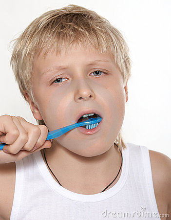 The boy cleans a teeth a tooth-brush. A background white