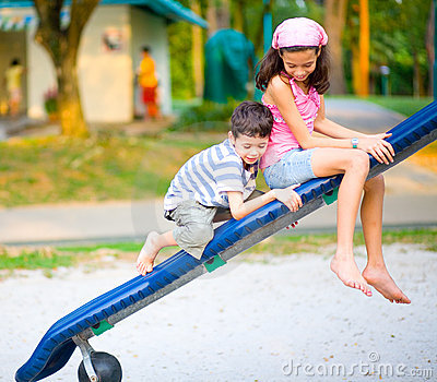 Boy climb on the slide with sister