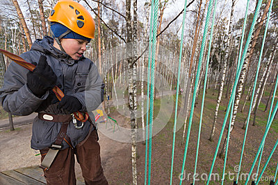 Boy climber preparing to the passage ropes course
