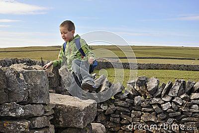 Boy climbing dry-wall in English countryside