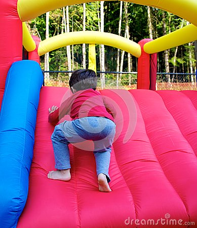 Boy climbing on inflatable castle