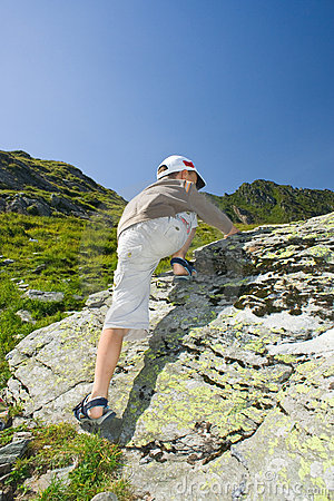 Boy climbing on mountain