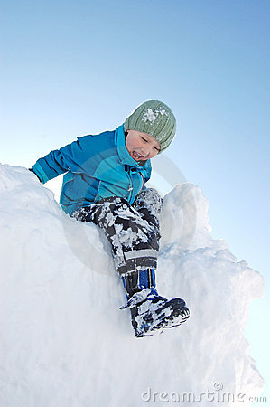 Boy climbing on snow pile