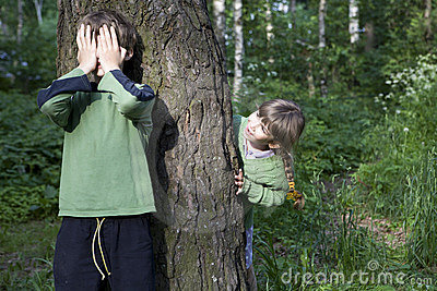 Boy close his eyes by hand. Girl look out tree.