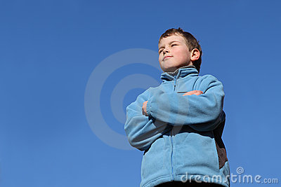 Boy with closed eyes in blue jacket, blue sky