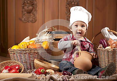 Boy in a cook cap among pans and vegetables