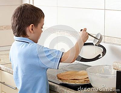 Boy cooking pancakes