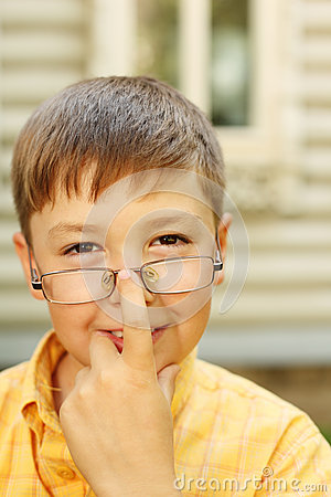 Boy corrects glasses near house