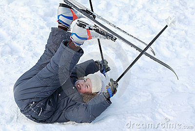 Boy with cross-country skis lying on snow