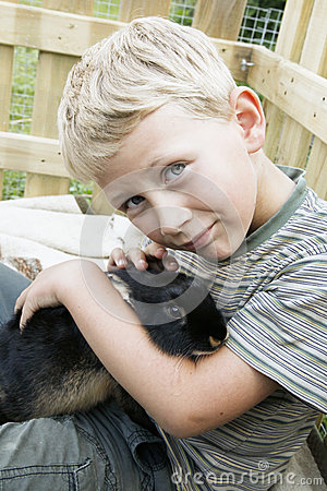 Boy cuddling up with pet rabbit