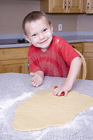 Boy cutting out cookie