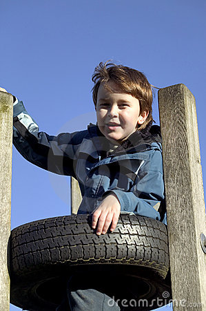 Boy cvlimbing a tyre tower