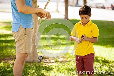 Boy and dad playing with a yo-yo