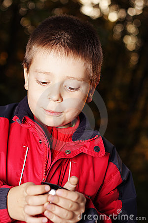 Boy in dark forest holding cup