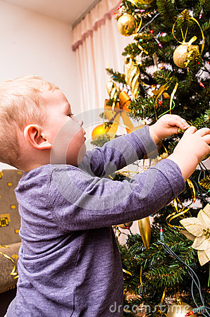 Boy decorates the Christmas tree