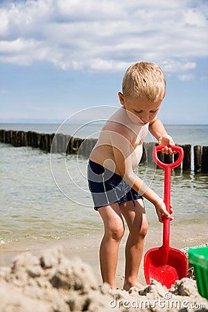 Boy dig in sand on beach