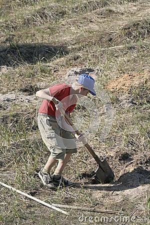 Boy digging in field