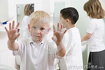 A boy displaying his hands in a school bathroom