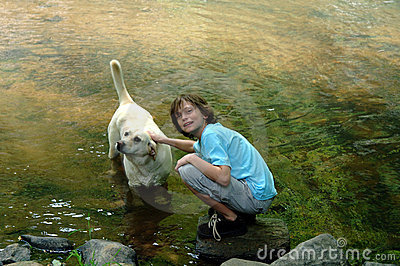 Boy and dog playing in river