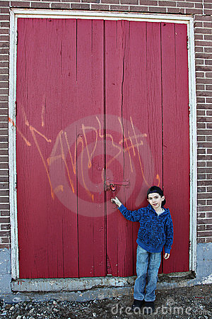 Boy by doors with graffiti