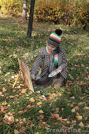 Boy drawing outdoor in autumn