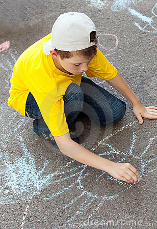 Boy draws on  asphalt