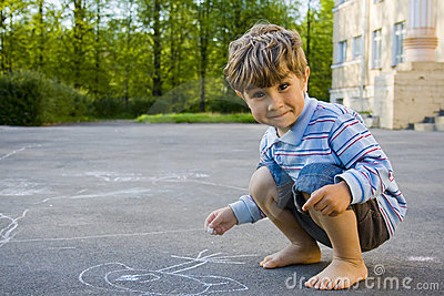 The boy draws with chalk