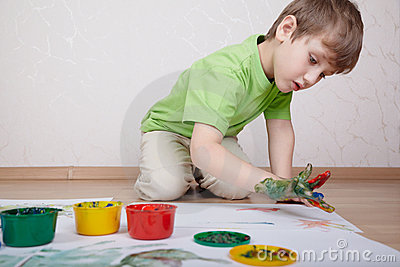 Boy draws color paints with his fingers