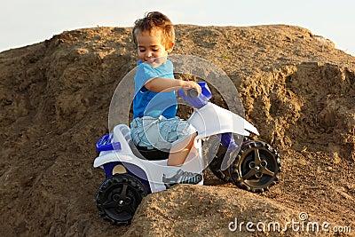 Boy driving toy quad on terrain
