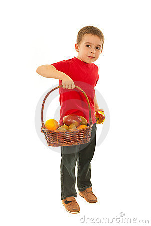Boy eating apple from basket