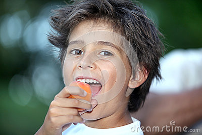 Boy eating an apricot