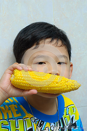 A boy eating boiled corn