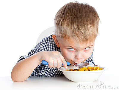 A boy is eating cereal from a bowl