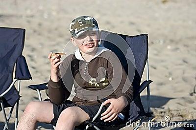 Boy eating sandwich on beach