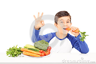 Boy eating vegetables and gesturing happiness seated at table