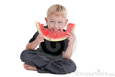 Boy eating a watermelon on the floor