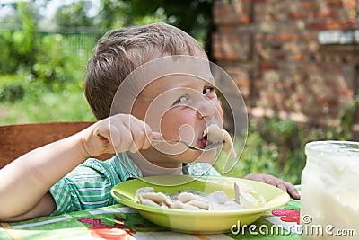 Boy eats breakfast outdoors