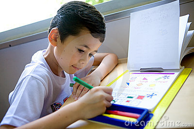 Boy engross doing his math coloring homework