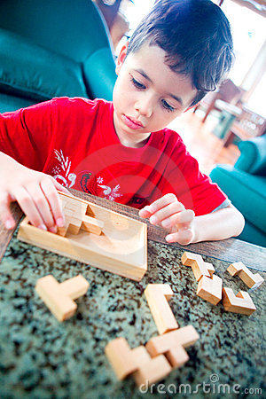 Boy engross on the wooden jigsaw game.