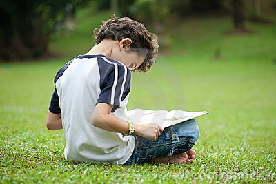 Boy enjoying his reading book in outdoor park