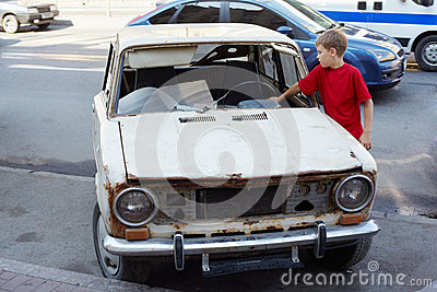 Boy examines rusty with broken windshield car