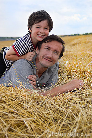 The boy and father on hay
