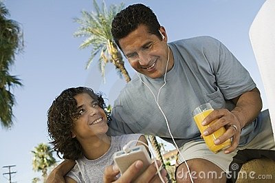 Boy and father holding portable music player