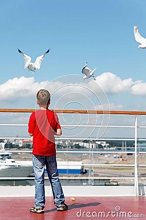 Boy feeds seagulsl on deck of ship.
