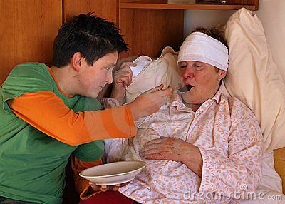 The boy feeds the sick woman