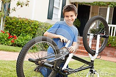 Boy fixing bike in garden