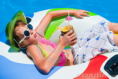 Boy floating in the swimming pool in hat