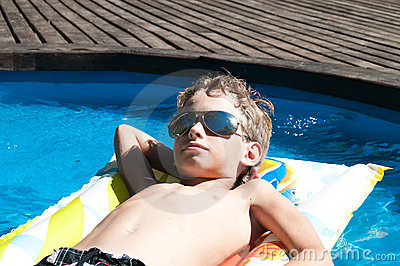 Boy floating in the swimming pool in sun glasses